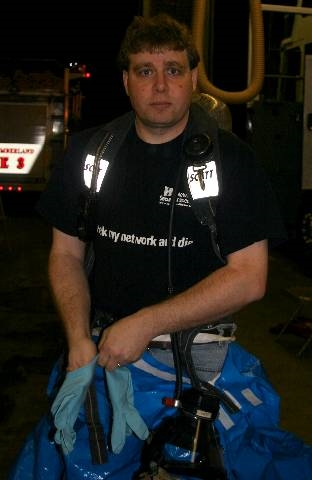 Andrew at the fire station wearing an airpack and putting on a class-b hazmat suit